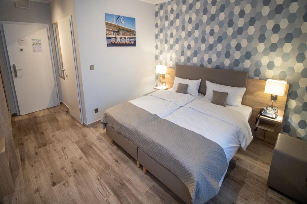 """Bett und Raumansicht des Doppelzimmers """"Komfort"""" im Hotel Fallersleber Spieker"""